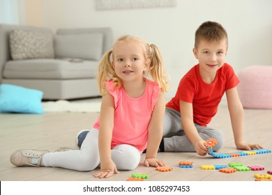 Cute little children playing with pazzles at home