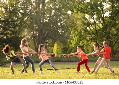 Cute little children playing with rope outdoors on sunny day