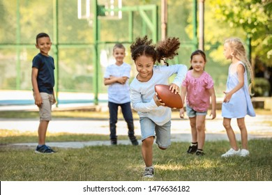 Cute little children playing with rugby ball in park
