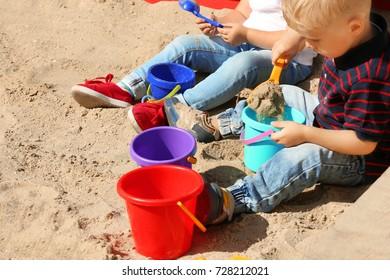 Cute little children playing in  sandbox, outdoors
