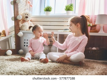 Cute little children are playing together. Happy girls at home. Funny lovely sisters are having fun in kids room.