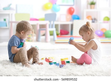 Cute little children playing while sitting on carpet at home