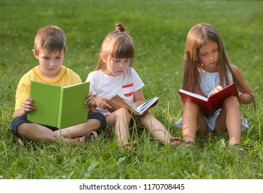 Cute little children reading books in park on summer day