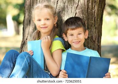 Cute little children reading books near tree in park