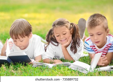 Cute little children reading books in park