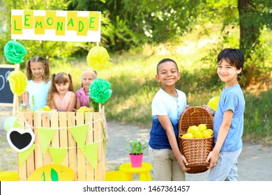 Cute little children selling lemonade in park