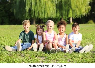Cute little children sitting on green grass outdoors