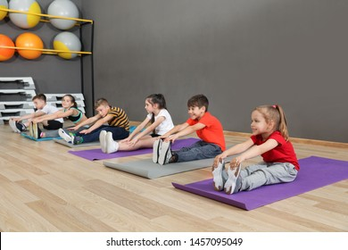 Cute little children sitting on floor and doing physical exercise in school gym. Healthy lifestyle
