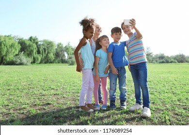 Cute little children taking selfie outdoors