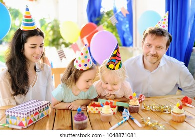 Cute little children twins and their parents having fun and celebrate birthday party with colorful decoration. Family with sweets, candy, whistle/blower/horn and festive gifts. Kid birthday party.