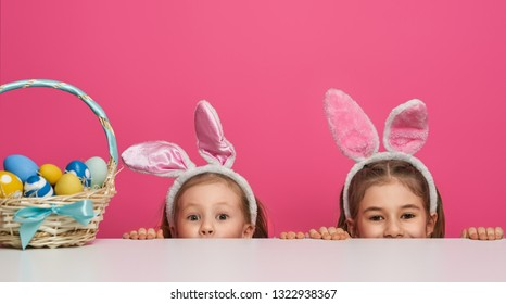Cute little children wearing bunny ears on Easter day. Girls with painted eggs on white and pink background.