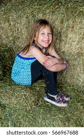 A cute little country girl in blue,  sits on a step outside the family barn