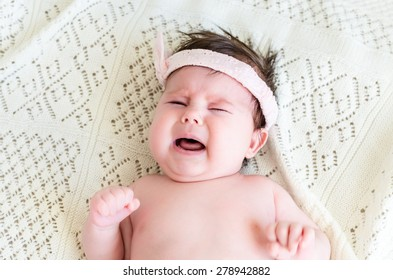 Cute little crying newborn baby girl seeking attention with crying and screaming, wearing in pink head bandage bow on her head on the background of woolen blanket