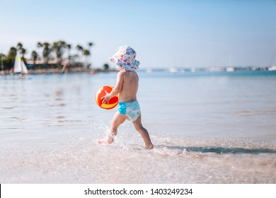 Cute little curly baby play with colorful ball on beach. Little girl walking on the water at the seaside. Enjoying a lovely summer day. Vacation concept