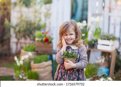 Cute little curly blonde toddler girl in red rubber boots posing in the garden among flowers