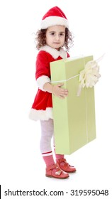 Cute little curly-haired girl in a suit and hat of Santa Claus holding hands in front of him a large box with a gift. -Isolated on white background