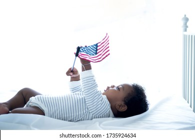 Cute little dark skinned is cute, holding American flag celebrating Independence day, with the American flag celebrate July 4