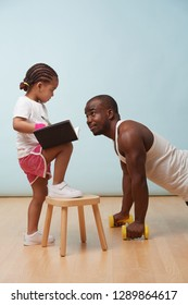 Cute little daughter fitness training her handsome black young father. She is making notes in her paper notebook. Child role play. He looks at her for approval. She looks at him sternly.