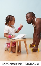 Cute little daughter fitness training her handsome black young father, making notes. Child role play. He looks at her, listening reproaches while she is commenting with her finger raised.