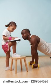 Cute little daughter fitness training her handsome black young father. She is making notes in her paper notebook. Child role play. He looks at her for approval.