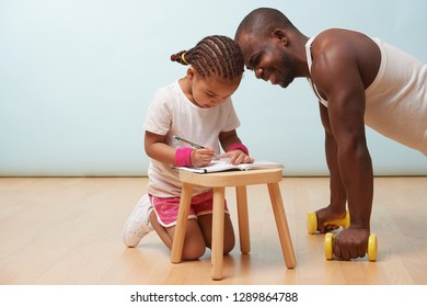 Cute little daughter fitness training her handsome black young father. She is making notes in her paper notebook. Father laughs about what he sees in there. Child role play.