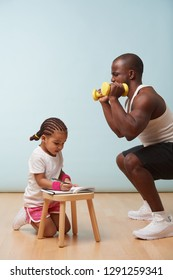 Cute little daughter fitness training her handsome black young father. She is making notes in her paper notebook. Child role play. He looks at her for approval, while making squats. Last push.
