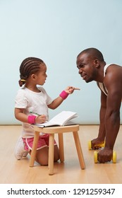 Cute little daughter fitness training her handsome black young father, making notes. Child role play. He looks at her, listening reproaches while she points at him her finger.