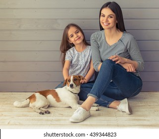 Cute little daughter and her beautiful young mother are looking at camera and smiling while posing with their dog