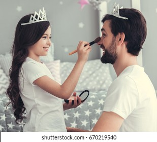 Cute little daughter and her handsome young dad in crowns are playing together in child's room. Girl is doing her dad a makeup