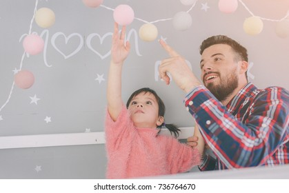 Cute little daughter and her handsome young dad iare playing together in child's room. Dady and child spend time together while sitting on the floor in bedroom