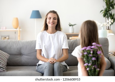 Cute little daughter hold flowers making surprise for mom greeting her with birthday, excited young mother sit on couch with eyes closed waiting getting gift from child, girl prepare present to mommy