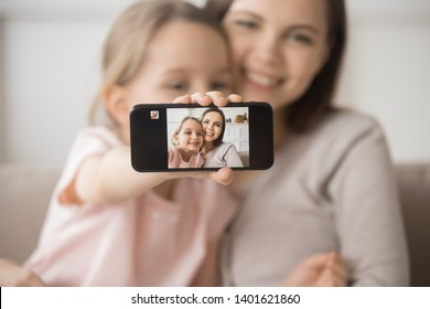 Cute little daughter hold smartphone make self-portrait picture hugging young smiling mom, happy mother or nanny and preschooler girl child cuddle embrace posing for cellphone selfie together