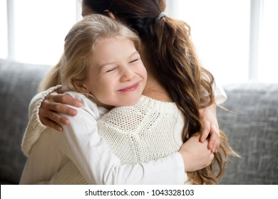 Cute little daughter hugging mother holding tight, mum and happy preschool or school girl cuddling, smiling sincere child embracing mommy, warm relationships and sweet pure kids love for mom concept