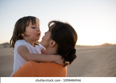 Cute little daughter kissing and hugging with her mother on sand dune during sunset