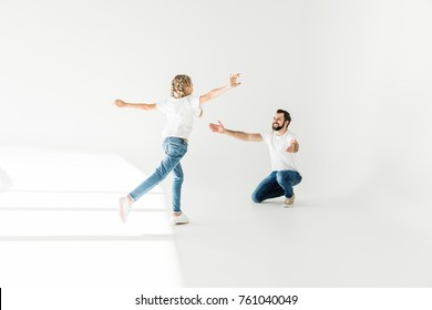 cute little daughter running to happy father with open arms on white