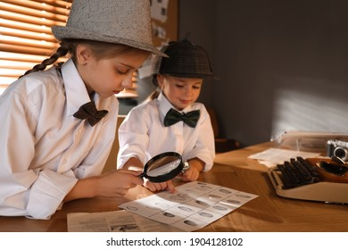Cute little detectives exploring fingerprints with magnifying glasses at table in office