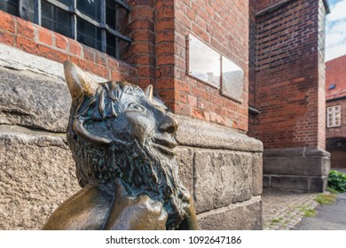 Cute little devil sitting on a stone outside Marienkirche (St. Mary s Church) in Luebeck, Schleswig-Holstein, northern Germany.