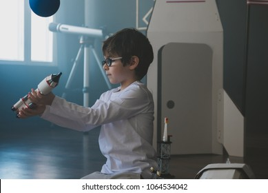 Cute little dreamer boy playing with toy rocket, dreaming of becoming an astronaut or scientist