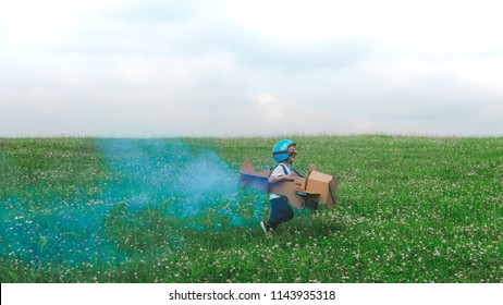 Cute little dreamer kid boy wearing blue helmet and aviator glasses flying in a cardboard airplane with attached smoke bombs through the field, pretending to be a pilot
