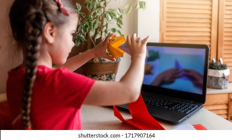 Cute little elementary schoolgirl doing origami fish with folded color paper looking video on laptop, online workshop, kids at-home activity, creativity and distant education, focus on hands