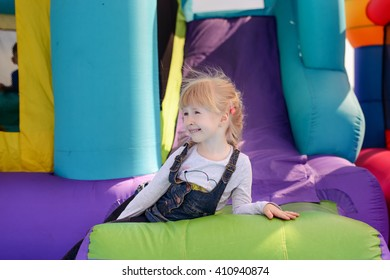 Cute little fair haired girl playing on a colorful bouncy castle at a fairground waving and smiling as she exits the slide
