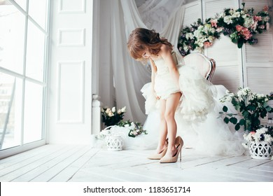Cute little fashionista in white dress. Happy child girl try on outfits and mom's shoes in decorated  light room with flowers and armchair. Near the panoramic window.