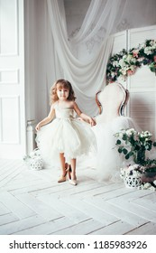 Cute little fashionista in white dress. Happy child girl try on outfits and mom's shoes in decorated  light room with flowers and armchair