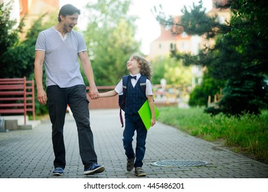 Cute little first grader is going with his father to school. Dad amused the boy to cheer him up. Father keep his son's hand. Behind the schoolboy's backpack. The boy is smartly dressed. B