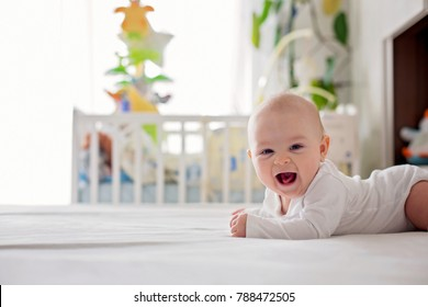 Cute little four month old baby boy, playing at home in bed in bedroom, soft back light behind him