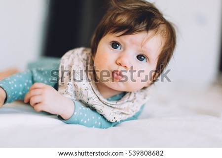 ebfb59dab Cute little four month old baby girl dressed in blue bodysuit looking into  the camera