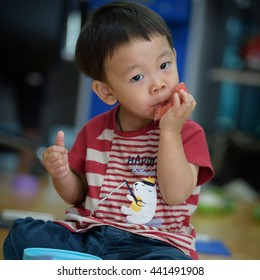 Cute little funny asian boy eat watermelon at home office