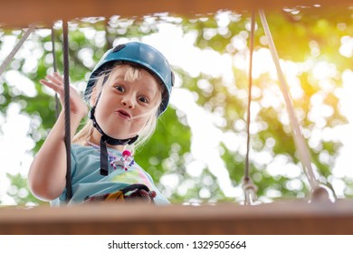 Cute little funny caucasion blond girl in helmet having fun walking by rope suspension bridge in adventure park. Children outdoor extreme sport activities concept