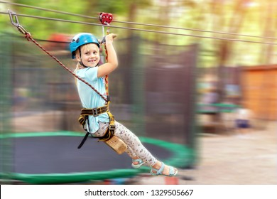 Cute little funny caucasion blond girl in helmet having fun riding rope zipline in adventure park. Children outdoor extreme sport activities concept