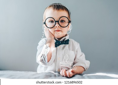 Cute little genius. Baby boy wearing smart outfit and eye glasses working as call center operator answering several people and drinking imaginery coffee. Children and technologies concept.